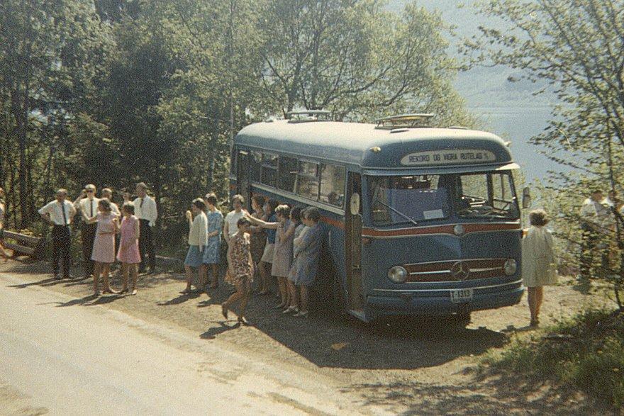 T-1313 fra Record og Vigra Rutelag på tur til Isfjorden med en forening fra Valderøya en flott sommerdag i 1968. Record og Vigra Rutelag hadde all flybusskjøring til og fra flyplassen på Vigra fra den ble åpnet i 1958 og frem til Ålesundstunnellene ble åpnet i 1987. I 1988 ble selskapet oppkjøpt at Ålesund Bilruter. RVR hadde to Mercedes-busser med reg.nr. T-1313. I 1962 kjøpte de en ny O321H fra Arna med 36 sitteplasser, men det viste seg at denne ble for liten. Året etter ble den solgt til en busselskap i Namsos, og en ny Mercedes O321HL, ble bestilt. Denne ble levert fra VBK/Arna i februar 1963, og hadde 44 sitteplasser. Kanskje noen av leserne vet hvilket selskap i Namsos som overtok første T-1313? Tekst: Tor Sindre Grønningsæter Foto: Torstein Remme