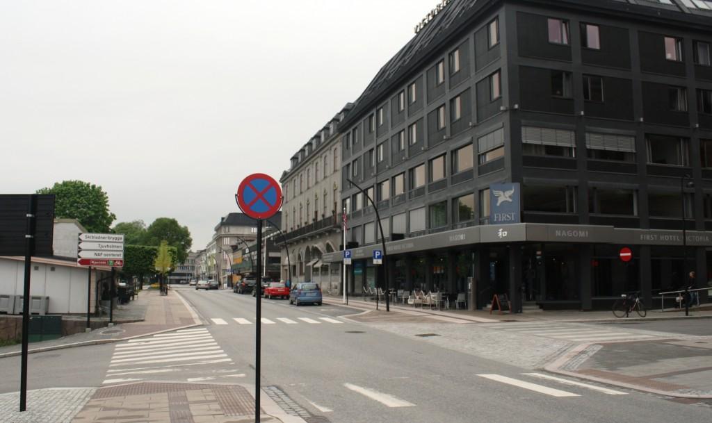Vi ser Strandgata nordover fra stasjonen med First Hotel Victoria til høyre. Jernbanelinja ligger til venstre parallelt med Strandgata. Det er innkjøring forbudt til hotellet fra denne siden. Dette er Enggata som er enveiskjørt i sentrum. Skal man sette av passasjerer ved hotellet, må man kan kjøre inn i Enggata fra andre enden, f.eks. fra Torggata. Det går også en vei ned til venstre. Dette er en jernbaneundergang som fører over til «sjøsiden» av Hamar. Dette er også veien til Tjuvholmen Kro, en utstikker i Mjøsa med flott oversikt over sentrum fra «sjøsiden».