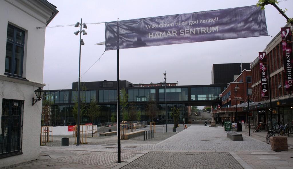 Dette er fra andre enden av Torggata og vi ser inn på Stortorget i Hamar. Hamars nye kulturhus er nettopp innviet, men det gjenstår enda noe arbeid før torgplassen er ferdig. Til venstre ser vi hjørnet av Stallgården som har vært der siden 1849. Rundt Stortorget er det nå bygninger fra alle epoker av byens historie.