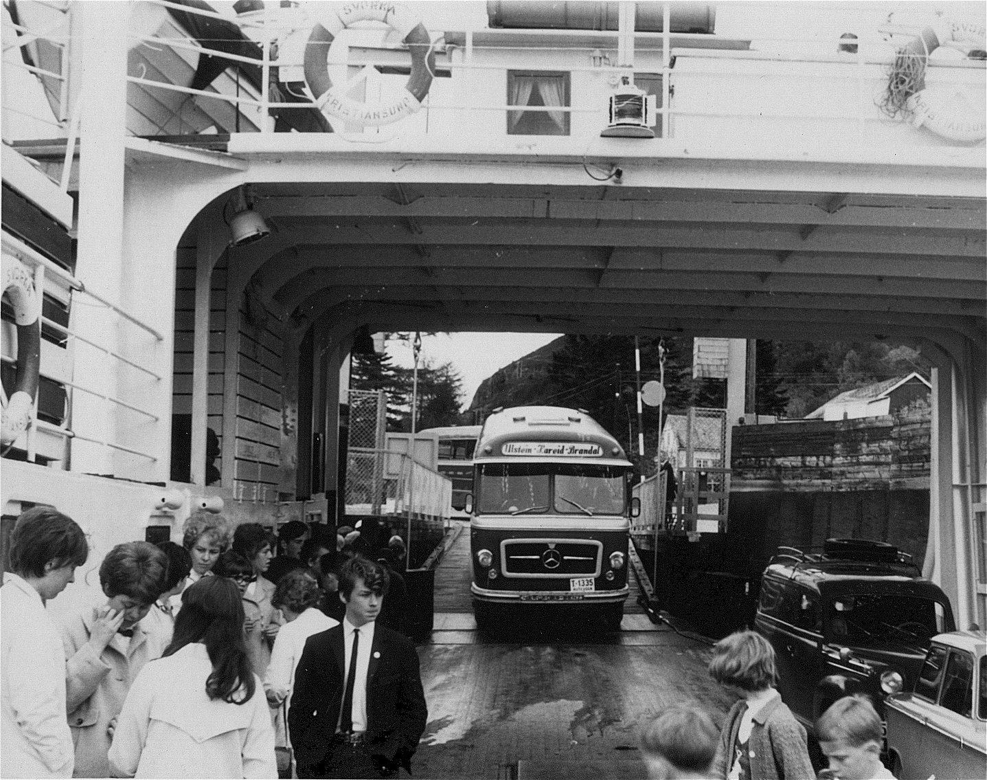 Ombordkøyring i Møre og Romsdal Fylkesbåtar si ferje B/F 'Svorka' ved Årvik ferjekai i Sande kommune. Bussane som er på turoppdrag tilhøyrer K. Moldskred Rutebiler i Ulsteinvik. Kolbjørn Moldskred dreiv med persontransport i Ulstein kommune frå 1930-talet, fram til sin død i 1976. Bedrifta vart vidare leia av sonen Arve Moldskred, og den vart fusjonert inn i Sørøy-Buss A/S som vart etablert i 1982. T-1335 er ein 1963-modell Mercedes-Benz LP321 med bygg nr. 142 frå Bussbygg på Hovdenakken i Romsdal. Sjåfør er Kåre K. Ulstein. Bussen som er i ferd med å køyre inn på ferja bak T-1335, er T-1098 - ein 1961-modell Mercedes-Benz O321HL, Moldskred sin andre hekkmotorbuss. Denne har bygg nr. 107 frå Bussbygg, 45 seter. Denne bussen vart seinare ombygt frå bagasjerom med fast vegg, til todørs-buss. Desse to bussane kom i fokus ved tariffstreikane i 1963. I april dette året vart det streik i 4 veker. T-1335 vart levert i juni, og rakk så vidt å kome i drift før det på ny braut ut sjåførstreik. Denne varte i om lag 3 veker, og då var det kun Kolbjørn Moldskred som arbeidsgjevar som kunne køyre. Med sonen Arve som billettør køyrde dei rutene mellom Ulsteinvik og Hareid med største bussen, som var `61-modellen T-1098. (Opplysningar frå Arve Moldskred, formidla av Ola A. Rangsæter)
